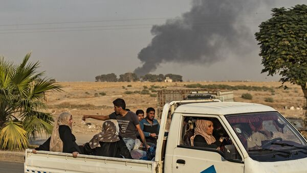 Civilians ride a pickup truck as smoke billows following Turkish bombardment on Syria's northeastern town of Ras al-Ain in the Hasakeh province along the Turkish border on October 9, 2019 - Sputnik International