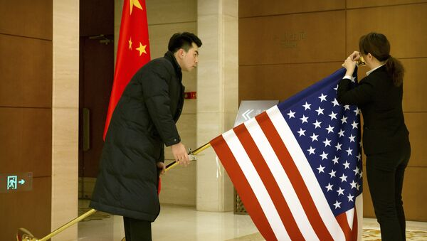 Chinese staffers adjust a US flag before the opening session of trade negotiations between the US and Chinese trade representatives at the Diaoyutai State Guesthouse in Beijing, 14 February 2019 - Sputnik International