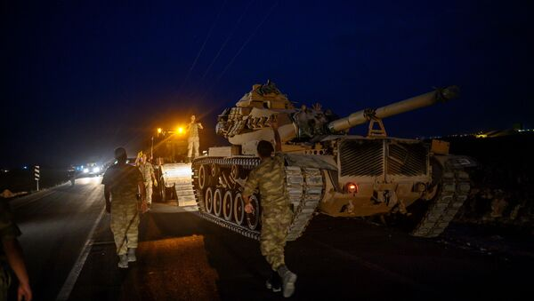 A Turkish army's tank drives down from a truck as Turkish armed forces drive towards the border with Syria near Akcakale in Sanliurfa province on October 8, 2019 - Sputnik International