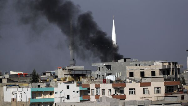 Smoke from a fire caused by an incoming mortar fired from the Syrian side, billows behind a mosque's minarets in Akcakale, Sanliurfa province, southeastern Turkey, smoke billows from targets inside Syria during bombardment by Turkish forces Thursday, Oct. 10, 2019 - Sputnik International