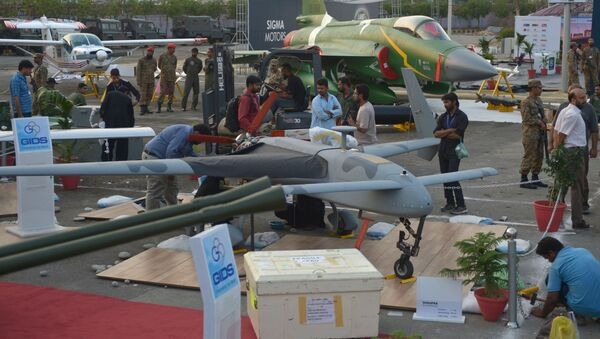 Pakistani officials prepare a locally-manufactured GIDS Shahpar unmanned aerial vehicle for display as a PAC JF-17 Thunder multirole combat aircraft, jointly developed by China and Pakistan, is seen in background at right during preparations for the International Defence Exhibition and seminar (IDEAS) in Karachi on November 29, 2014 - Sputnik International