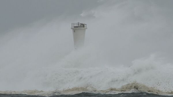 Surging waves hit against the breakwater and a lighthouse as Typhoon Hagibis approaches at a port in the town of Kiho, Mie prefecture, central Japan. - Sputnik International
