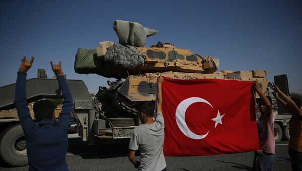 Local residents applaud as a convoy of Turkish forces trucks transporting tanks is driven in Sanliurfa province, southeastern Turkey, at the border with Syria - Sputnik International