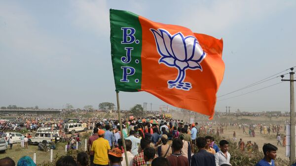 Indian supporters of the Bharatiya Janata Party (BJP) carry a party flag on their way to attend a campaign rally while wearing masks of Indian Prime Minister Narendra Modi ahead of the national elections in Siliguri on April 3, 2019 - Sputnik International