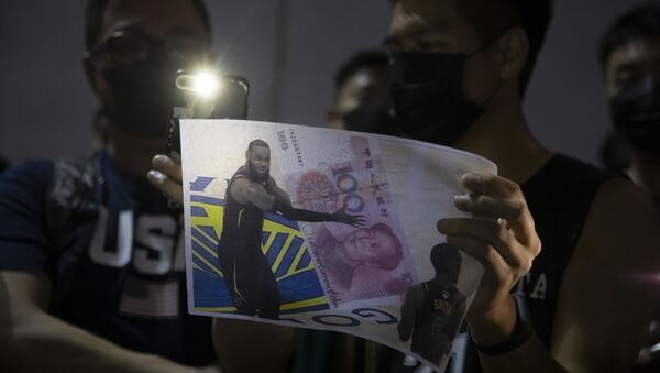 A demonstrator holds a sign showing Lebron James embracing a Chinese 100-yuan banknote during a rally at the Southorn Playground in Hong Kong, Tuesday, Oct. 15, 2019 - Sputnik International