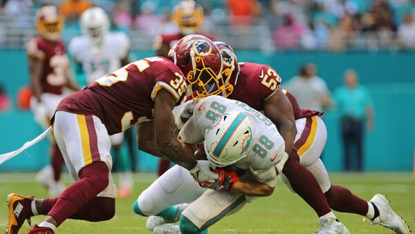 Oct 13, 2019; Miami Gardens, FL, USA; Miami Dolphins tight end Mike Gesicki (88) carries the ball and gets tackled by Washington Redskins strong safety Montae Nicholson (35) and linebacker Jon Bostic (53) during the fourth quarter of the game at Hard Rock Stadium. - Sputnik International