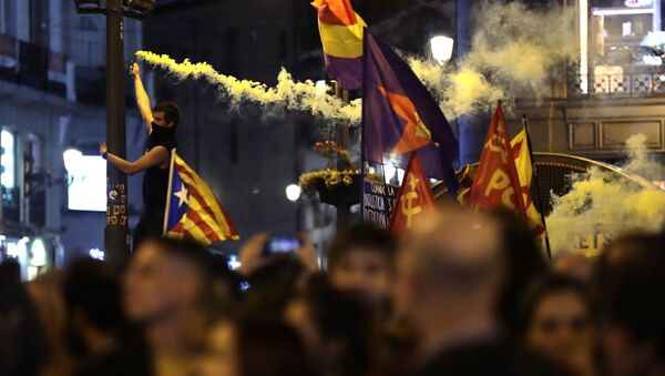 A protestor burns a flare as a pro-independence Estelada flag is waved in Puerta del Sol square in Madrid, Spain, Wednesday, Oct. 16, 2019.  - Sputnik International