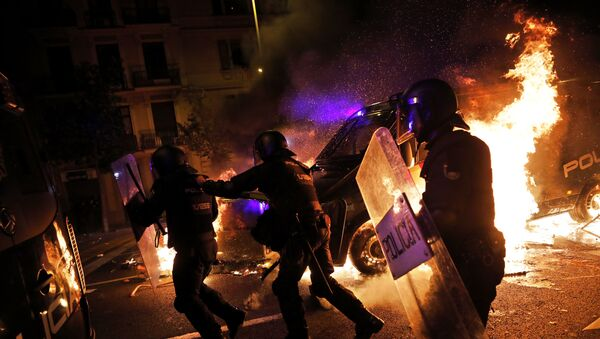 Policemen run as a police van catches fire during clashes between protestors and police in Barcelona, Spain, Wednesday, Oct. 16, 2019. Spain's government said Wednesday it would do whatever it takes to stamp out violence in Catalonia, where clashes between regional independence supporters and police have injured more than 200 people in two days. - Sputnik International