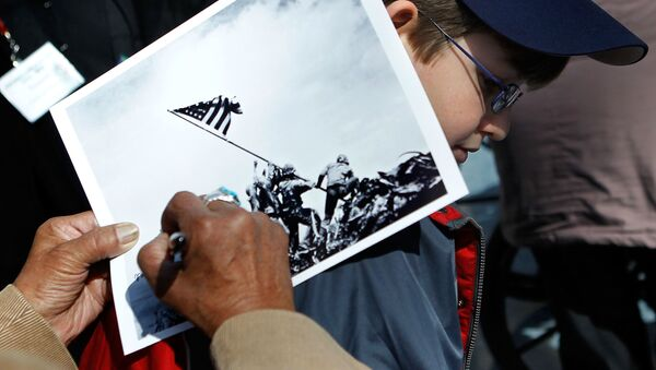 An Iwo Jima veteran signs autograph on the famous WWII photograph Raising the Flag on Iwo Jima shot by AP photographer Joe Rosenthal for Michael Scott of Altoona, Pennsylvania, at a ceremony to mark the 65th anniversary of the battle of Iwo Jima February 19, 2010 at the National Museum of Marine Corps in Triangle, Virginia - Sputnik International