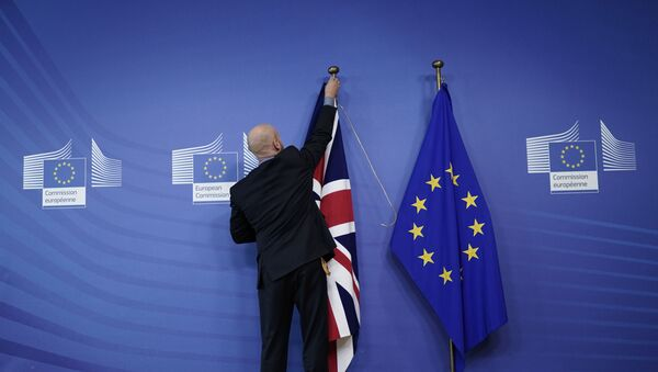 An official hangs a Union Jack next to an European Union flag at EU Headquarters in Brussels on October 17, 2019, ahead of a European Union Summit on Brexit. - Sputnik International