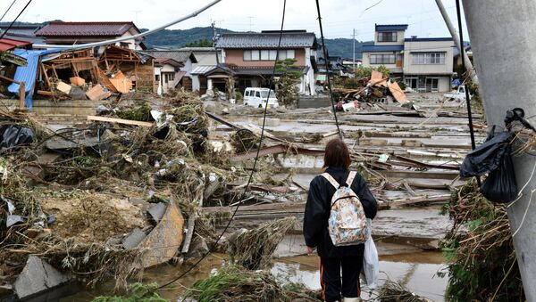 A woman looks at flood-damaged homes in Nagano on October 15, 2019, after Typhoon Hagibis hit Japan on October 12 unleashing high winds, torrential rain and triggered landslides and catastrophic flooding. - Rescuers in Japan worked into a third day on October 15 in an increasingly desperate search for survivors of a powerful typhoon that killed nearly 70 people and caused widespread destruction.  - Sputnik International