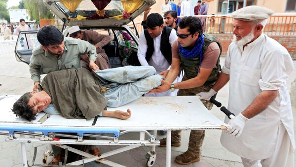 Men carry an injured person to a hospital after a bomb blast at a mosque, in Jalalabad, Afghanistan October 18, 2019 - Sputnik International