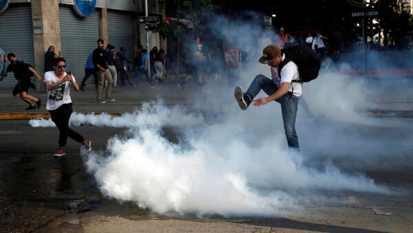 A demonstrator kicks a tear gas canister during a protest against the increase in the subway ticket prices in Santiago, Chile, October 18 - Sputnik International