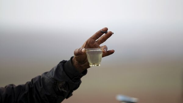 A worker shows off the final fuel product at a makeshift oil refinery site in the Syrian town of Marchmarin in southern Idlib region, 16 December 2015. - Sputnik International