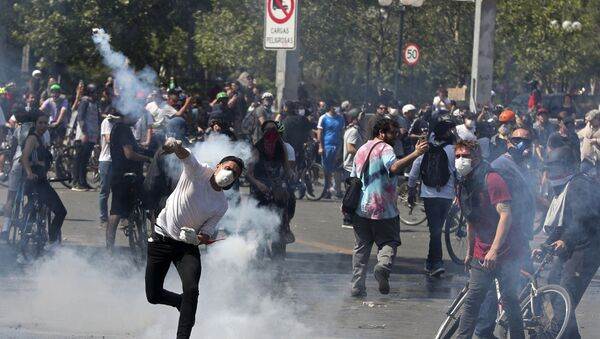 A protester returns a tear gas canister to police during clashes in Santiago, Chile, Sunday, Oct. 20, 2019. - Sputnik International