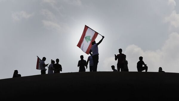Anti-government protesters wave a Lebanese flag, as they stand on the Dome City Center known as The Egg, an unfinished cinema leftover from the civil war, as they watch other protesters, in downtown Beirut, Lebanon, Sunday, Oct. 20, 2019. - Sputnik International