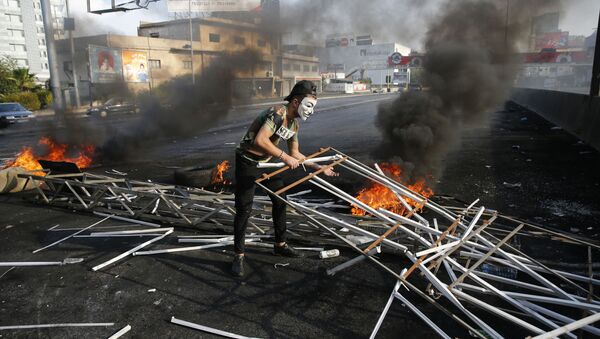 An anti-government protester adds to a makeshift barricade blocking a highway that links to north Lebanon in east Beirut, Lebanon, Sunday, Oct. 20, 2019 - Sputnik International