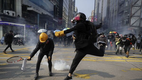 Protesters throw away the tear gas canisters fired by riot policemen during a rally in Hong Kong, Sunday, Oct. 20, 2019 - Sputnik International