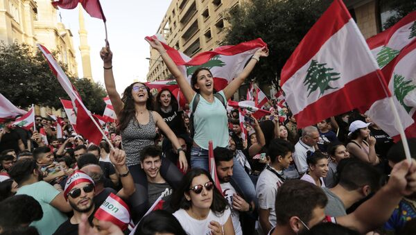 Anti-government protesters shout slogans in Beirut, Lebanon, Sunday, Oct. 20, 2019. Tens of thousands of Lebanese protesters of all ages gathered Sunday in major cities and towns nationwide, with each hour bringing hundreds more people to the streets for the largest anti-government protests yet in four days of demonstrations. - Sputnik International