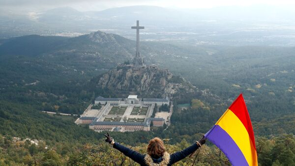 A woman holds the Spanish republican flag as she looks down on the Valley of the Fallen memorial - Sputnik International