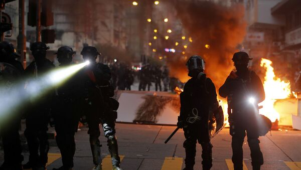 Police officers stand next to a burning barricade during an anti-government protest in Hong Kong China - Sputnik International