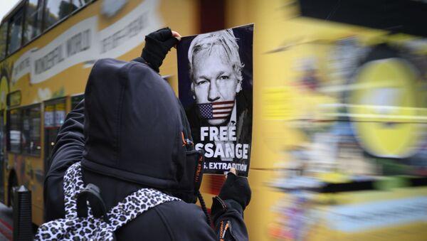 A protester holds a leaflet demanding the release of Julian Assange - Sputnik International