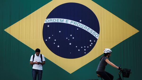 A man checks his mobile phone as a woman riding a bike passes next to a big Brazilian flag in Sao Paulo, Brazil June 28, 2018 - Sputnik International