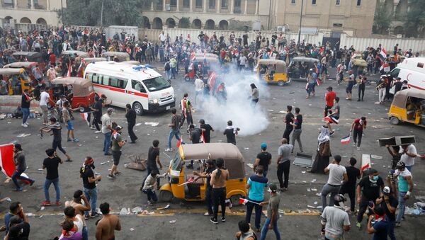 Demonstrators disperse as Iraqi Security forces use tear gas during a protest over corruption, lack of jobs, and poor services, in Baghdad, Iraq October 25, 2019 - Sputnik International