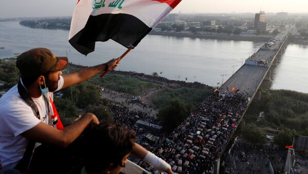 A demonstrator holds an Iraqi flag as he sits on a building during an anti-government protests in Baghdad, Iraq October 30, 2019 - Sputnik International