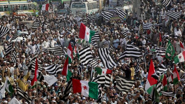 Supporters of religious and political party Jamiat Ulema-i-Islam-Fazal (JUI-F) wave flags as they listen to the speech of their leaders while heading towards Islamabad city, during what they call Azadi March (Freedom March) to protest the government of Prime Minister Imran Khan in Lahore, Pakistan October 30, 2019 - Sputnik International