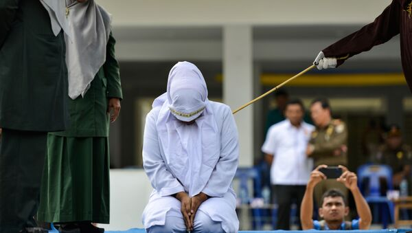A woman is whipped in public by a member of the Sharia police in Banda Aceh on October 31, 2019, after being caught having an affair with Aceh Ulema Council (MPU) member Mukhlis.  - Sputnik International