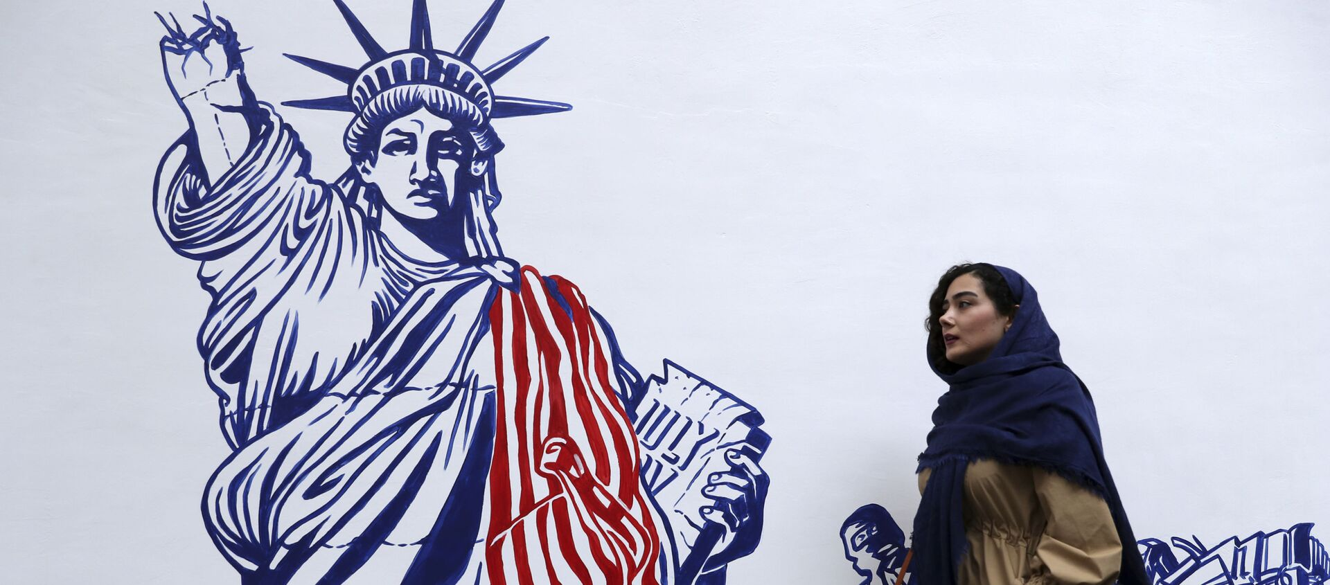 A woman walks past a satirical drawing of the Statue of Liberty after new anti-U.S. murals on the walls of former U.S. embassy unveiled in a ceremony in Tehran, Iran, Saturday, Nov. 2, 2019.  - Sputnik International, 1920, 29.08.2021