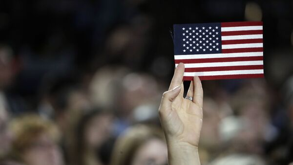 A small American flag is held aloft during Democratic presidential nominee Hillary Clinton's election night rally in the Jacob Javits Center glass enclosed lobby in New York, Tuesday, Nov. 8, 2016. - Sputnik International