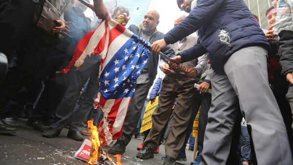 Iranian protesters set a US flag on fire during a rally outside the former US embassy in the Iranian capital Tehran on November 4, 2019, to mark the 40th anniversary of the Iran hostage crisis. - Sputnik International