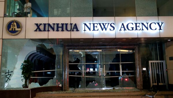 Damaged entrance of China's official Xinhua news agency is seen during anti-government protest in Hong Kong - Sputnik International