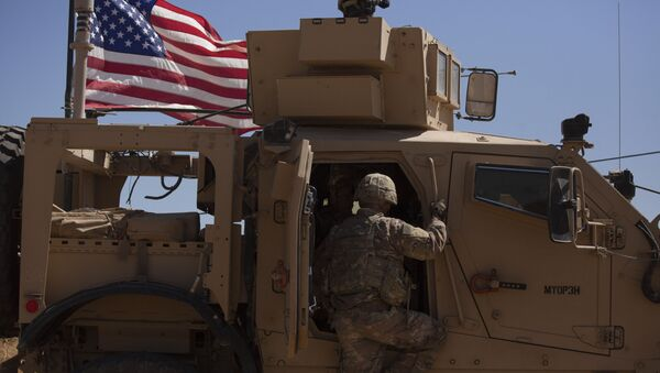 In this Sept. 8, 2019, photo, a U.S. soldier climbs into an armored vehicle during the first American-Turkish joint patrol in the so-called safe zone on the Syrian side of the border with Turkey near Tal Abyad, Syria - Sputnik International