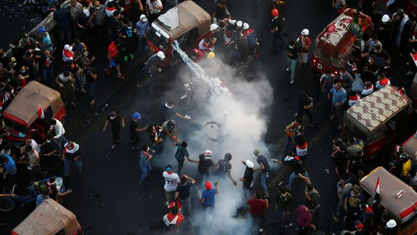Demonstrators try to put out a tear gas canister during an anti-government protests in Baghdad - Sputnik International