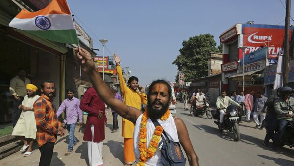 A Hindu devotee waves an Indian national flag and celebrates a verdict in a decades-old land title dispute between Muslims and Hindus, in Ayodhya, India , Saturday, Nov. 9, 2019.  - Sputnik International