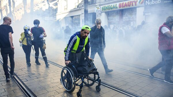 A man pushes his wheelchair away from teargas on Novemebr 9, 2019 in the center of Montpellier, southern France, during a demonstration as part of an nationwide anti-government protest called by the yellow vest movement (gilets jaunes). - Sputnik International