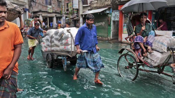 Bangladeshi men pull a loaded cart through a waterlogged street after heavy rainfall in Dhaka, Bangladesh, Saturday, May 21, 2016.  - Sputnik International