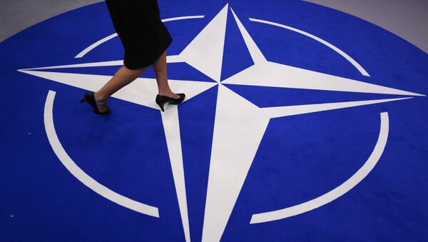 A woman walks across a carpet with the NATO logo ahead of the NATO (North Atlantic Treaty Organization) summit, at the NATO headquarters in Brussels, on July 11, 2018 - Sputnik International
