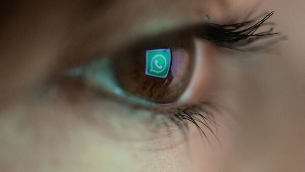 An illustration picture taken on March 22, 2018 in Paris shows a close-up of the WhatsApp logo in the eye of an AFP staff member posing while she looks at a flipped logo of WhatsApp - Sputnik International
