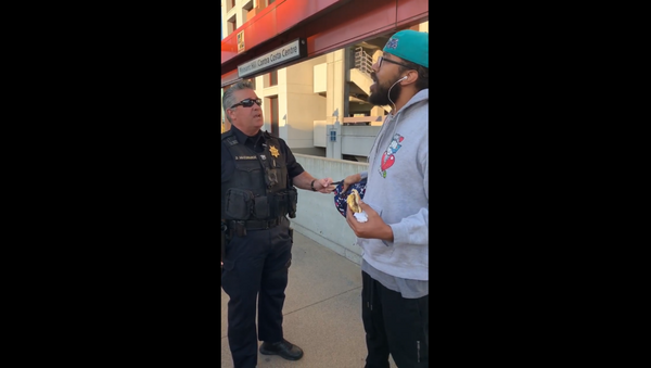 A BART officer from California is seen in cellphone footage confronting transit rider Steve Foster over his decision to eat a breakfast sandwich on the train platform, which is a citable offense per the state's law. - Sputnik International