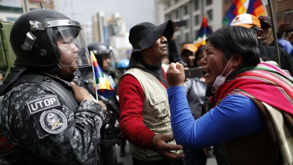A supporter of Bolivia's former President Evo Morales yells at a police officer, telling him to respect the nation's indigenous people in La Paz, Bolivia, Tuesday, Nov. 12, 2019. Former President Evo Morales, who transformed Bolivia as its first indigenous president, flew to exile in Mexico on Tuesday after weeks of violent protests, leaving behind a confused power vacuum in the Andean nation. (AP Photo/Natacha Pisarenko) - Sputnik International