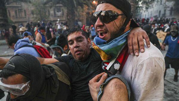 An injured anti-government demonstrator in Santiago - Sputnik International