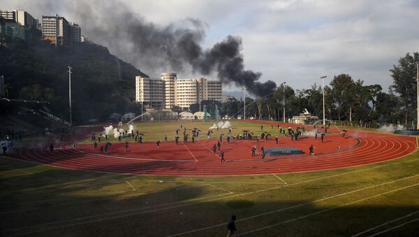 Students try to clear the tear gas canisters on a field during a face-off with police at Chinese University in Hong Kong, Tuesday, Nov. 12, 2019 - Sputnik International