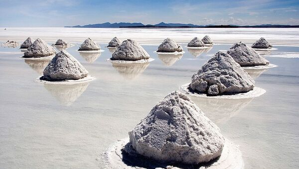 Salt mounds in Salar de Uyuni, Bolivia. The Salar de Uyuni is the world's largest (12 000 km²) and highest (3 700 m) salt flat, ca. 25 times as large as the Bonneville Salt Flats. It's the remnant of a prehistoric lake surrounded by mountains without drainage outlets. Salt is harvested in the traditional method: the salt is scraped into small mounds for water evaporation and easier transportation, dried over fire, and finally enriched with iodine. - Sputnik International