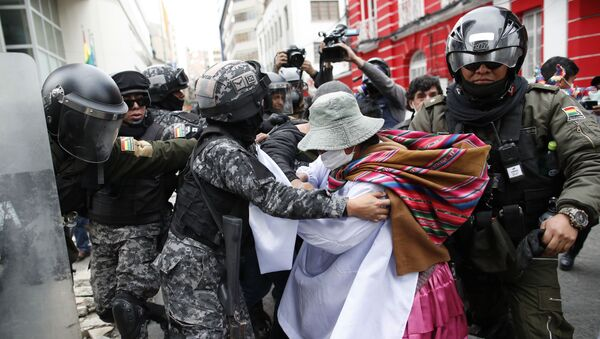 A backer of former President Evo Morales scuffles with police in La Paz, Bolivia, Wednesday, Nov. 13, 2019. The opposition senator who has claimed Bolivia's presidency Jeanine Anez, faces the challenge of stabilizing the nation and organizing national elections within three months at a time of political disputes that pushed Morales to fly off to self-exile in Mexico after 14 years in power.  - Sputnik International