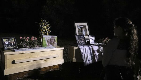 A young girl looks at the coffins with the remains of Rhonita Miller and four of her children, who were among the nine victims killed on November 4 in an attack authorities have blamed on a drug cartel, on their way to their burial at the cemetery of La Mora Ranch in the municipality of Bavispe, Sonora State, Mexico, on November 7, 2019 - Sputnik International