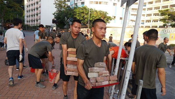 Personnel from the Chinese People's Liberation Army barracks in Hong Kong emerged on to the city streets on November 16, 2019, to help the clean-up after a week of violence and disruption caused by pro-democracy protesters. - In a rare and highly symbolic movement by a garrison which is confined to the barracks under Hong Kong's mini-constitution, scores of men with crewcuts and identical gym kits conducted a lightning-quick removal of bricks and debris near their base. - Sputnik International